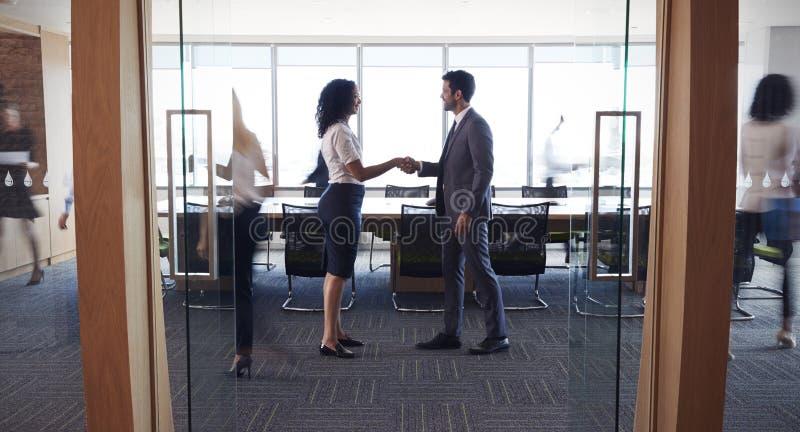Wirtschaftler, die Hände im Eingang zum Sitzungssaal rütteln lizenzfreies stockbild