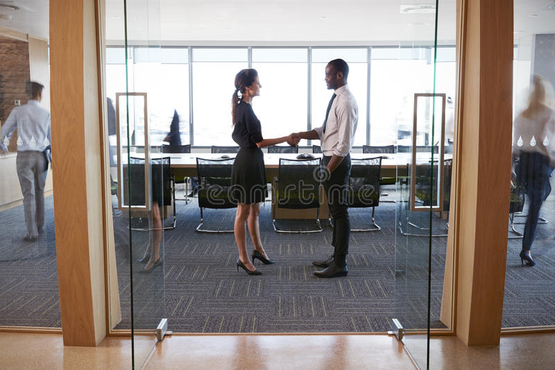 Wirtschaftler, die Hände im Eingang zum Sitzungssaal rütteln lizenzfreie stockfotografie