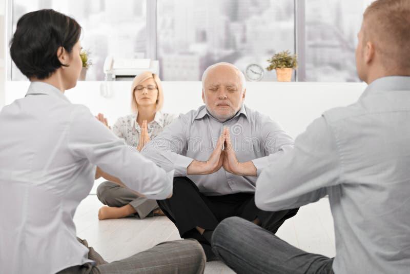 Wirtschaftler, die Yoga im Büro ausüben stockfotografie