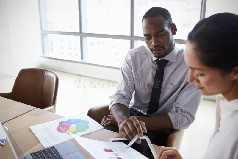 Wirtschaftler, die zusammen an Laptop im Sitzungssaal arbeiten stockfoto