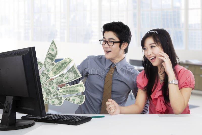 Wirtschaftler erwerben Geld online auf Computer lizenzfreies stockfoto