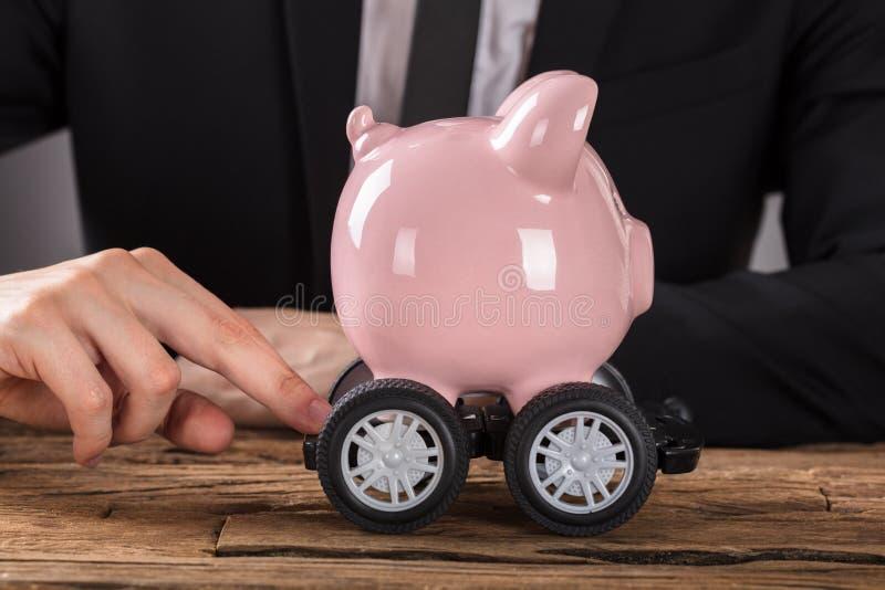 Wirtschaftler Pushing Piggy Bank auf Rädern stockfotos