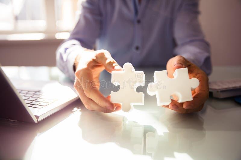 Wirtschaftler ` s Hand, die Puzzlen zwei hält stockbilder