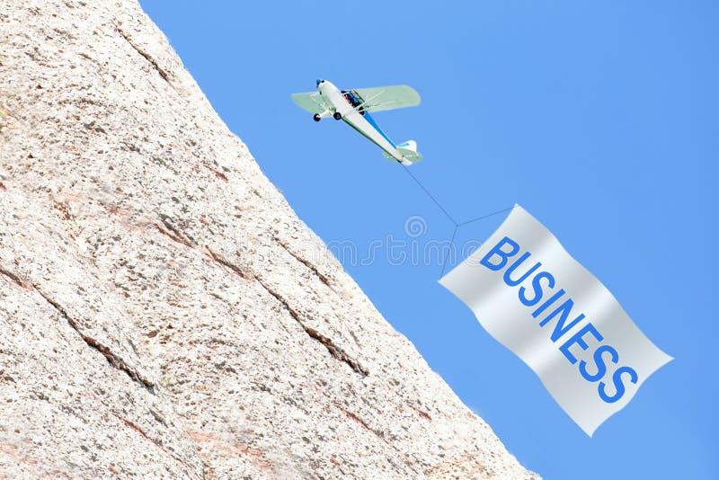 Wirtschaftler um riesigen Pfeil oben zeigend Flugzeug, das Fahne mit GESCHÄFT im Himmel zieht lizenzfreie stockfotografie