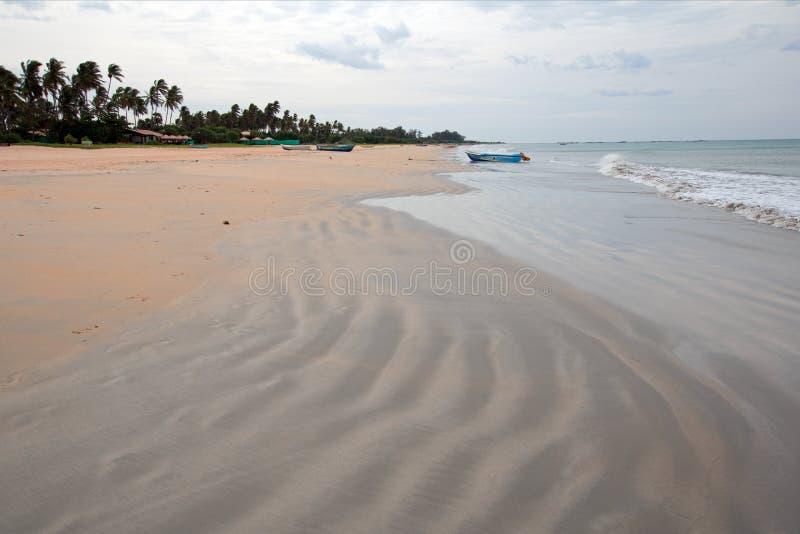 Wirujący wężowatego piasek wzory na Nilaveli Wyrzucać na brzeg z łodzią w Trincomalee Sri Lanka zdjęcia stock