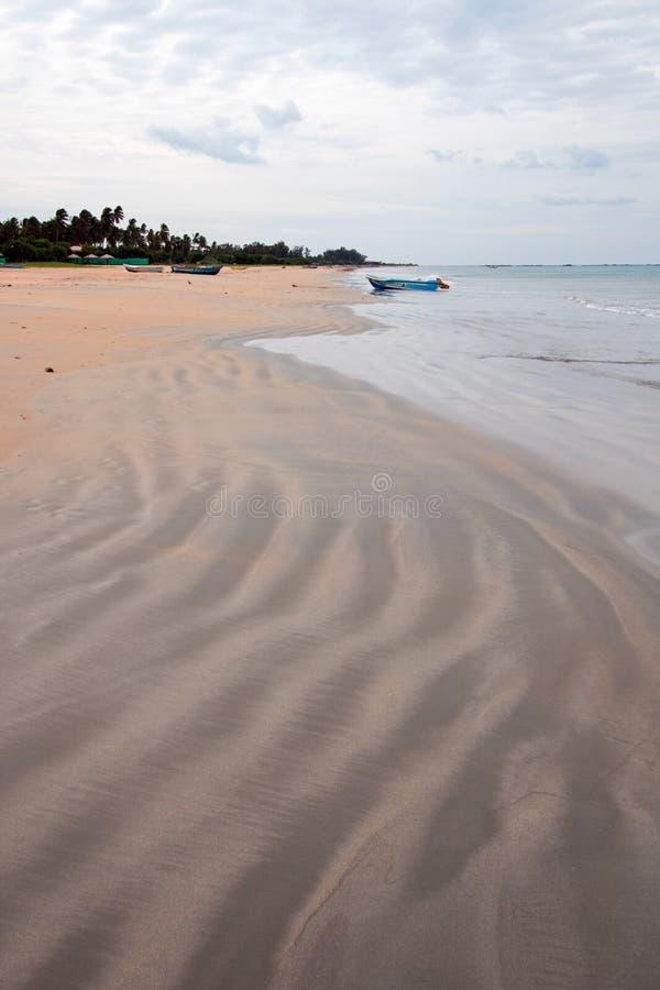 Wirujący wężowatego piasek wzory na Nilaveli Wyrzucać na brzeg z łodzią w Trincomalee Sri Lanka fotografia stock
