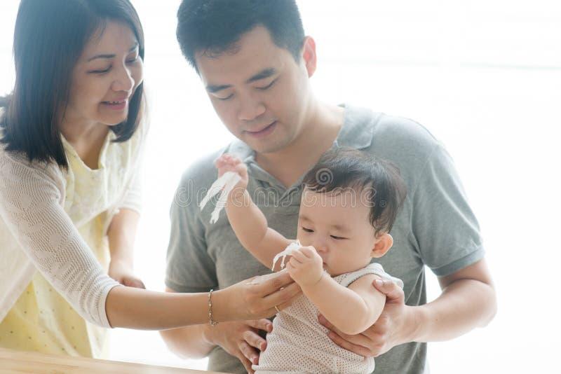 Wischt Babygesicht mit Gewebe ab lizenzfreie stockbilder