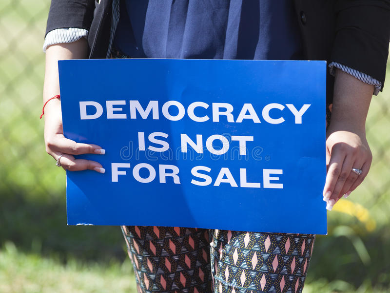 Wisconsin Governor Scott Walker Presidential Announcement Protest. WAUKESHA, WI/USA - July 13, 2015: A woman holds a protest sign in front of the Waukesha royalty free stock photo