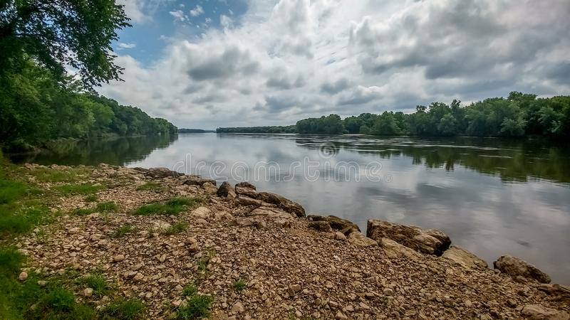 Wisconsin River with Rocky Shoreline. The Wisconsin River with a rocky shoreline and beautiful clouds reflected in the river stock images
