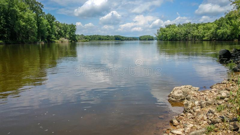 Wisconsin River with Rocky Shoreline. The Wisconsin River with a rocky shoreline and beautiful clouds reflected in the river stock photos