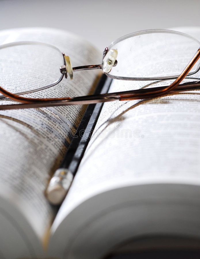 Wisdom. Closeup of open book, reading glasses and pencil royalty free stock photography