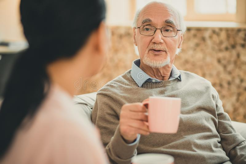 Wise old man with pink cup speaking to brown-haired lady. Having pleasant time. Wise old men with pink cup speaking to brown-haired lady spending time in living stock photography