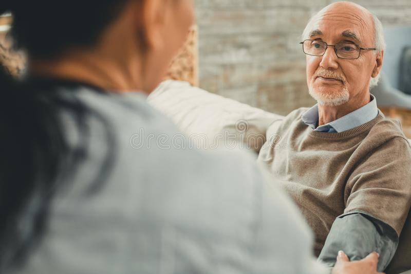 Wise senior directly looking on his doctor while she working with him. Blood pressure measured. Wise senior directly looking on his doctor while she working with royalty free stock photography