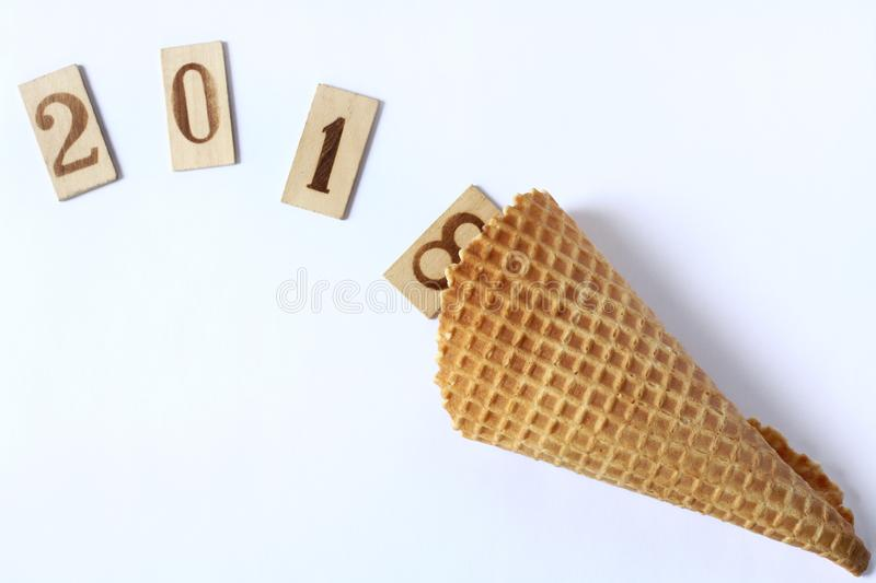 Wish abundance 2018. Wooden numbers drop out their waffle horn on a light surface top view stock images