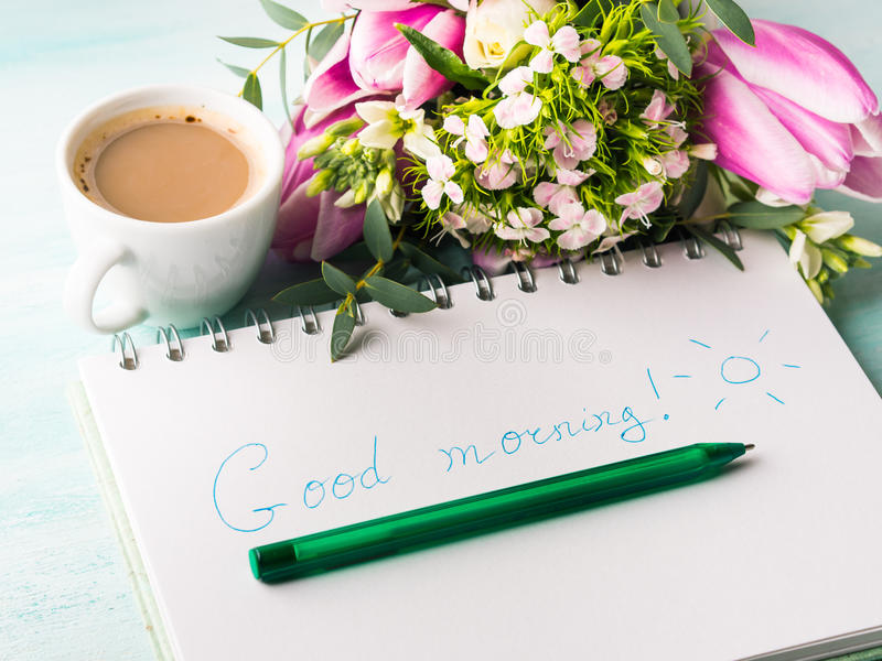 Wish good morning on notebook page and coffee. Wishing good morning hand written on notebook page and cup of coffee flowers. Spring summer breakfast still life royalty free stock images