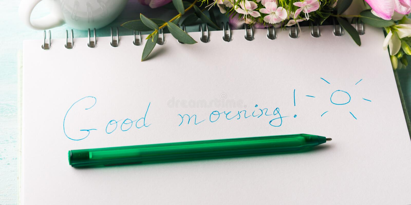Wish good morning on notebook page and coffee. Wishing good morning hand written on notebook page and cup of coffee flowers. Spring summer breakfast still life stock photos