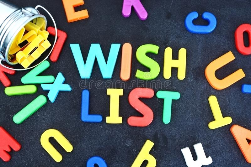 Wish list concept with colorful letters on blackboard pouring out from a metallic bucket royalty free stock photo