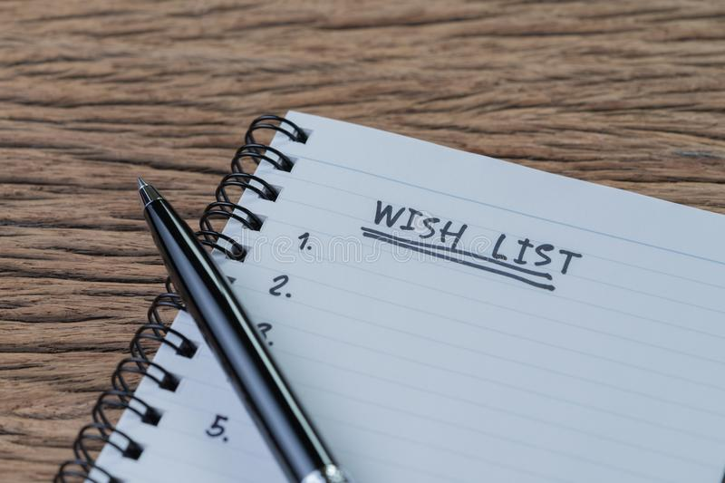 Wish list concept, pen on white paper note pad with handwritten stock photos