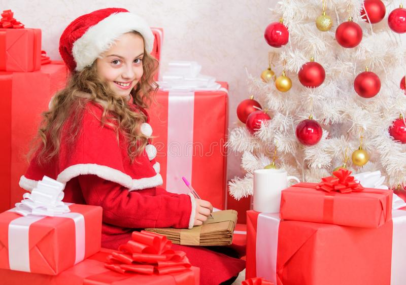 Wish list. Girl little kid hold pen and paper near christmas tree writing letter. I was good girl all year. Child write. Letter to santa claus. Child santa stock photos