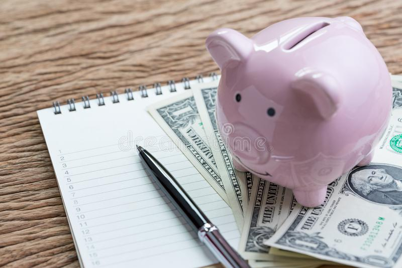 Wish list, shopping, revenue and expense or saving habit, select. Ived focus on paper notepad with number listed, pen and pink piggy bank on money US dollar stock images