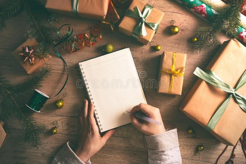Wish list on table with wrapped Christmas gift royalty free stock photography