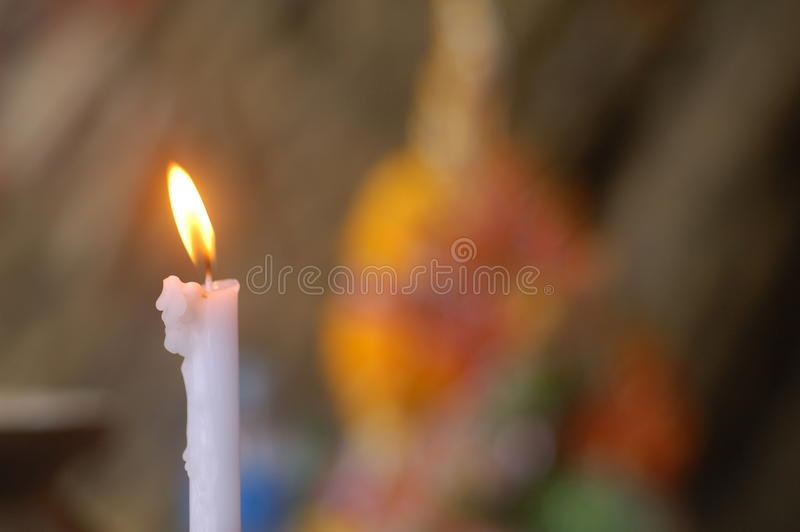 A wish. Lit candle at a small shrine by the beach royalty free stock photography