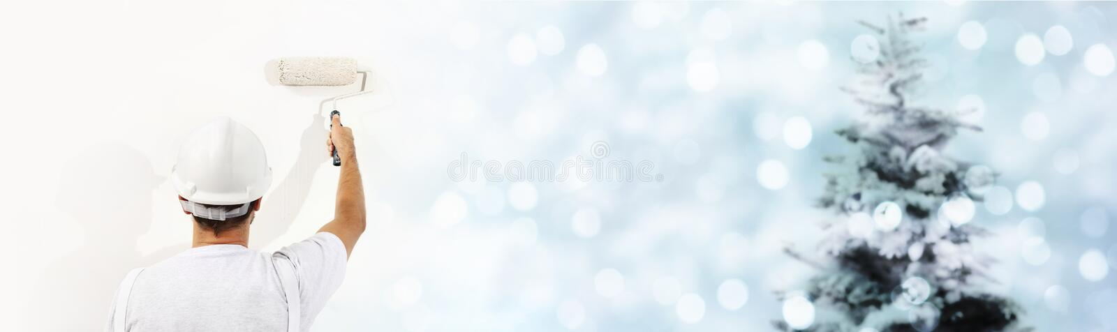 Wish a Merry Christmas concept, painter with roller painting a C royalty free stock image