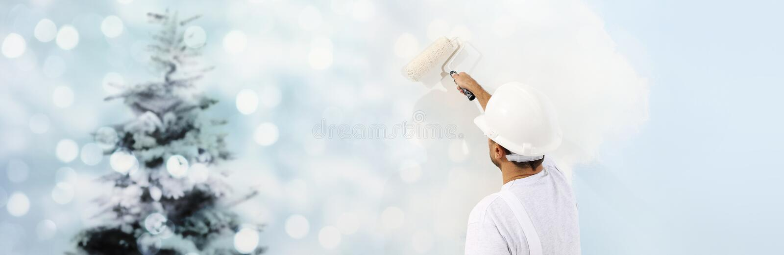 Wish a Merry Christmas concept, painter with roller painting a C stock photo