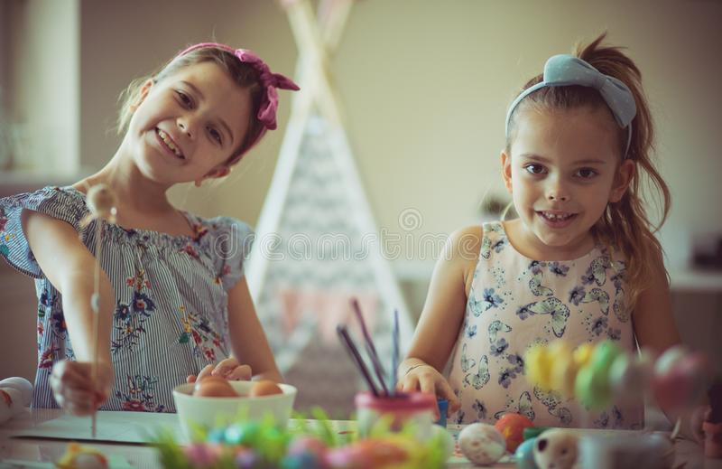 We wish you a happy Easter. Little girls coloring Easter egg stock photos