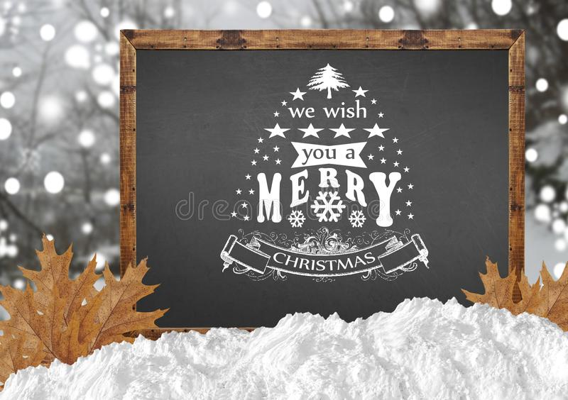 We Wish You A Merry Christmas on blackboard with blurr forest and leaves. Close stock photo