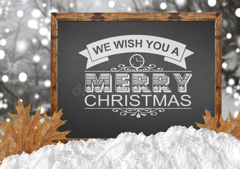 We Wish You A Merry Christmas on blackboard with blurr forest leaves. Close stock images