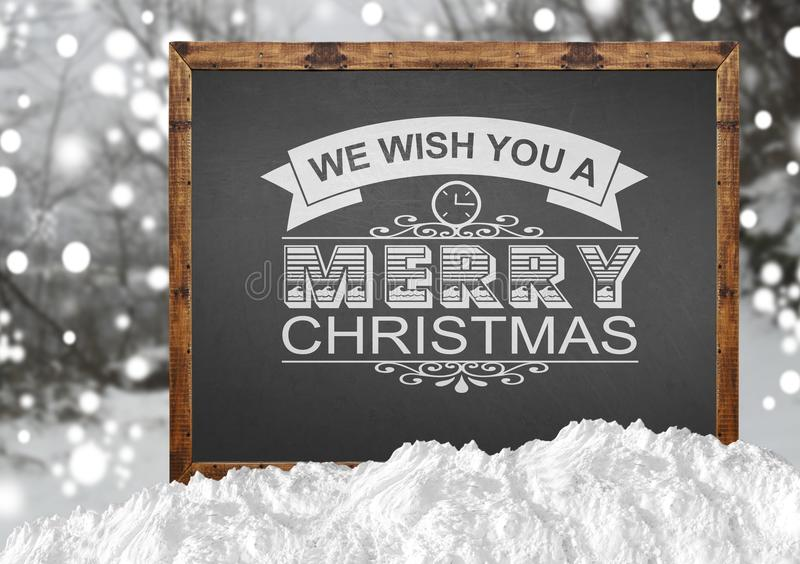 We Wish You A Merry Christmas on blackboard with blurr forest and snow. Close stock image