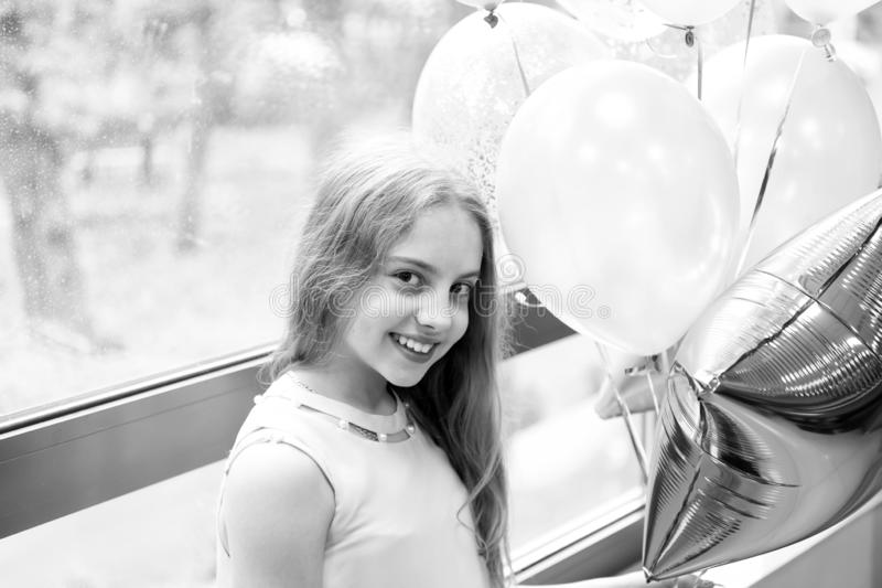 Wishing a happy holiday. Happy small child enjoying her birthday holiday. Adorable little girl celebrating holiday with. Party balloons. Joy and cheer, its a royalty free stock photo