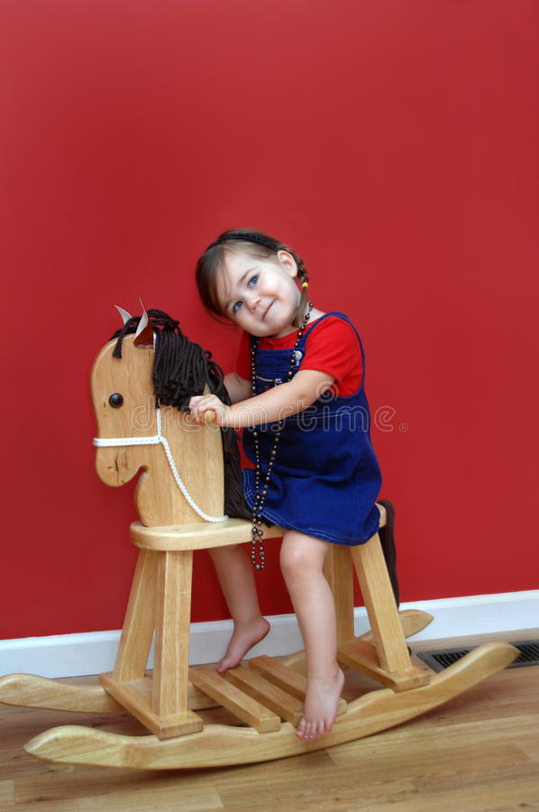 Wishing for a Real Horse. Little girl rides her wooden rocking horse and dreams of one day having a real horse. Walls are deep red and little girl is wearing a stock images