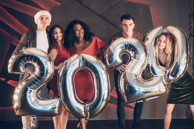 Wishing well. Group of beautiful young friends with inflatable numbers in hands celebrating new 2020 year royalty free stock photography