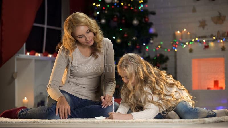 Wishlist alegre da escrita da mamã e da filha antes das preparações do feriado do Natal fotografia de stock