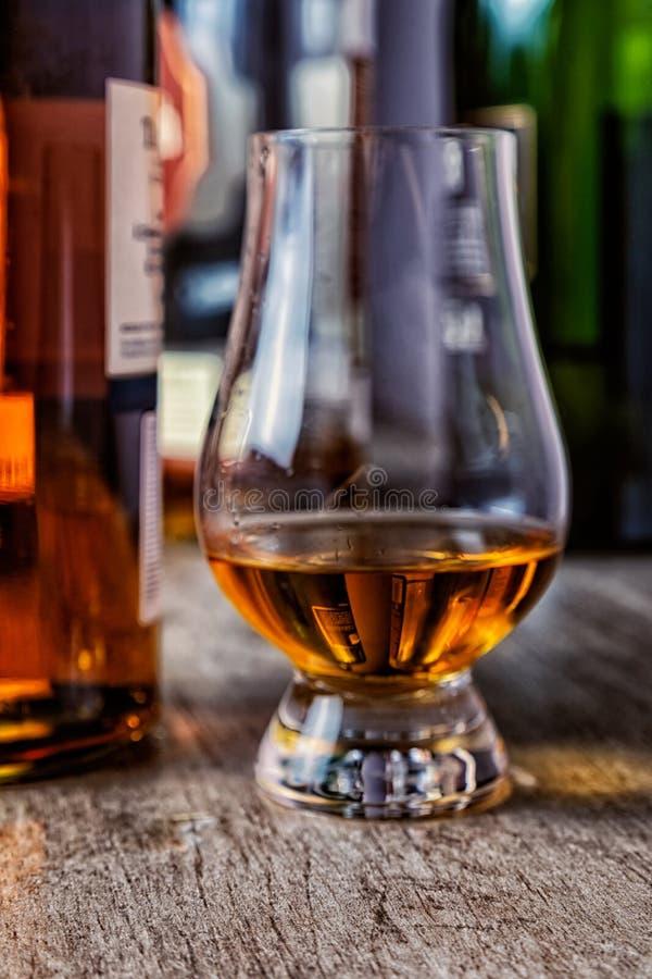 Wiskyglas met enig mout Schots op houten lijst en Schotse flessen stock afbeeldingen