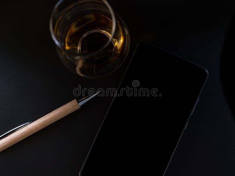Wiskyglas met houten hierboven pen en smartphone van royalty-vrije stock foto's