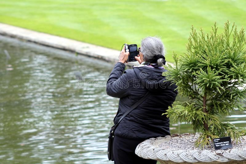 Wisley, Surrey, Reino Unido - 30 de abril de 2017: Vista posterior de tomar de la mujer fotografía de archivo