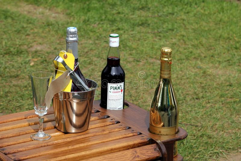 Wisley, Surrey, UK - April 30 2017: Stylish wooden drinks table, with a bottle of Pimms Strawberry Limited Edition, and two champ stock image