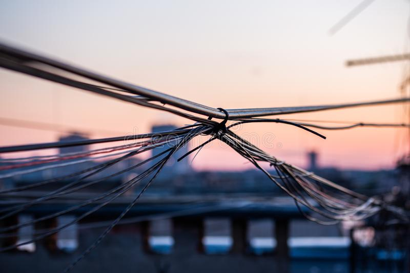 A wisp of wires on evening city roof with selective focus. And boke blur royalty free stock images