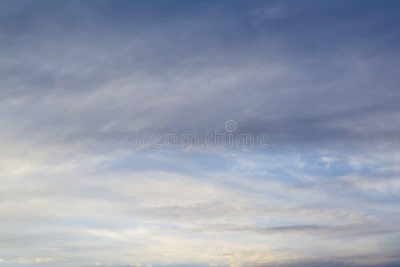 Wispy Doorzichtige Wolken tegen Verdonkerende Blauwe Hemel Achtergrond stock afbeeldingen