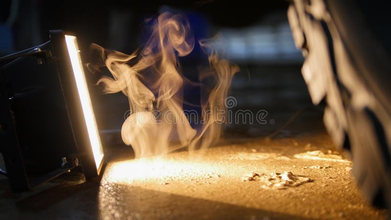 Wispy jet of smoke comes from the floor. Yellow light from the lamp royalty free stock photo
