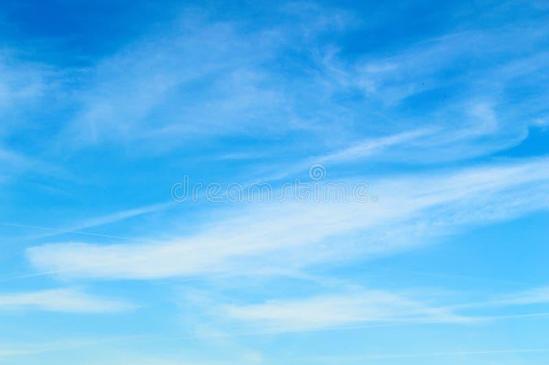 Wispy moln mot en härlig blå himmel arkivbilder