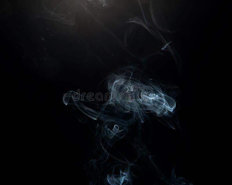 Wispy rök och fina partiklar med en obetydlig Lens signalljus över en svart bakgrund royaltyfri foto