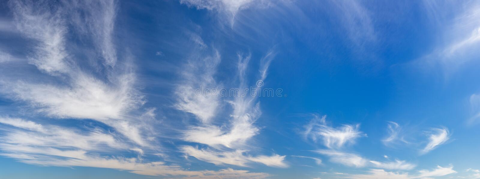 Wispy, soft clouds panorama across blue sky royalty free stock photo
