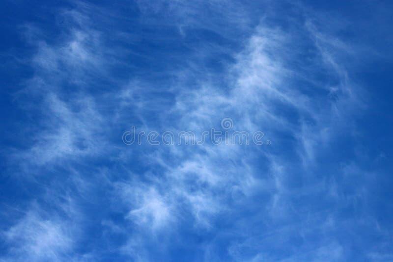 Wispy witte wolk tegen blauwe hemel op een zonnige dag stock fotografie