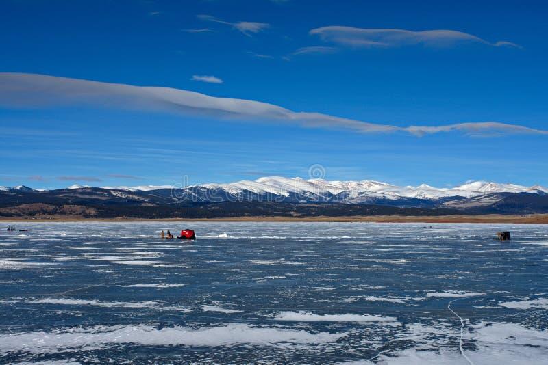 Wispy Wolken, die unten auf Eisfischern schauen stockfotos