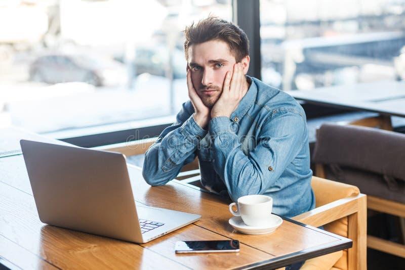 Wissen Sie nicht! Porträt des deprimierten müden bärtigen jungen Freiberuflers der Traurigkeit im Blue Jeans-Hemd sitzen allein i lizenzfreies stockbild