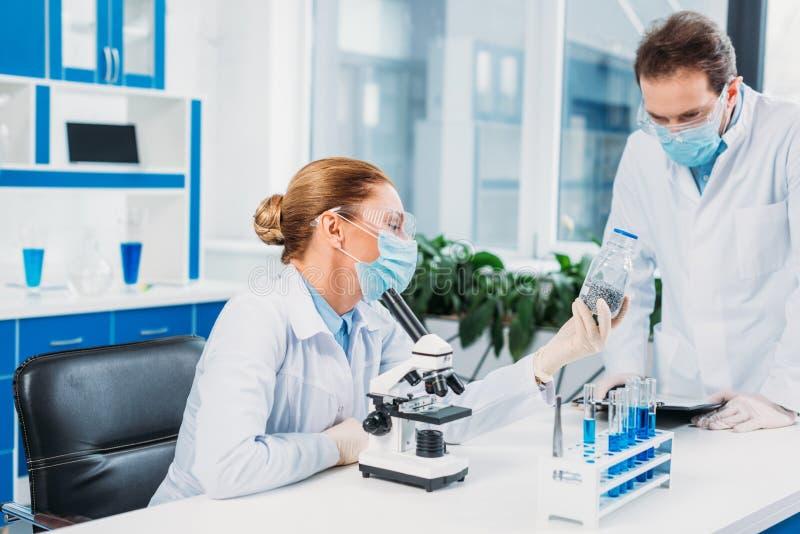 Wissenschaftler in den weißen Mänteln und Schutzbrillen, die mit Reagenzien und Mikroskop arbeiten stockfoto